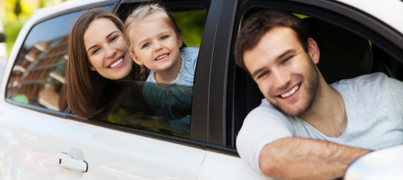 happy family posing inside their white car