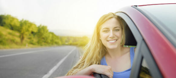 beautiful woman driving a car hire on a country road
