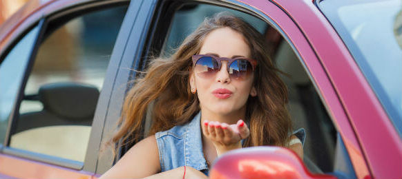beautiful young brunette woman with long hair wearing sun glasses inside a car hire