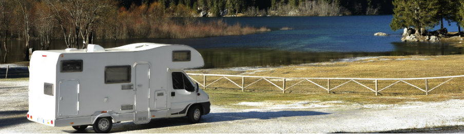 white campervan parked near the lake