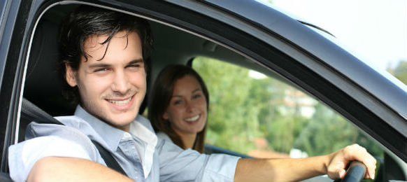 cheerful couple driving car rental