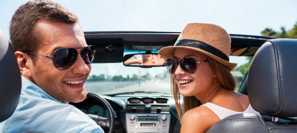happy travelers driving a convertible hire car
