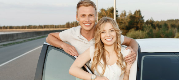 couple posing inside their car