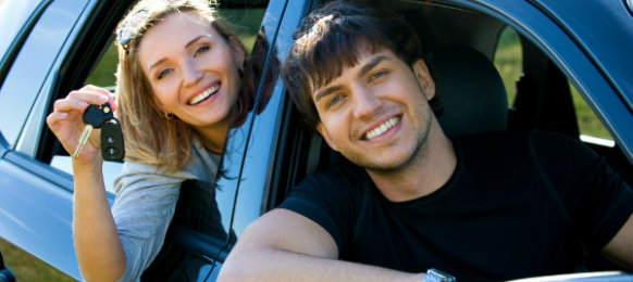smiling couple posing inside their blue car