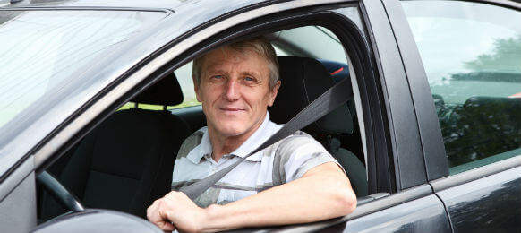 fastened smiling Caucasian senior man sitting in a car hire on driver seat