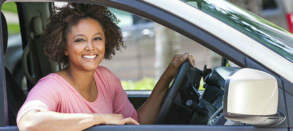 smiling female tourist with curly hair driving a rental car