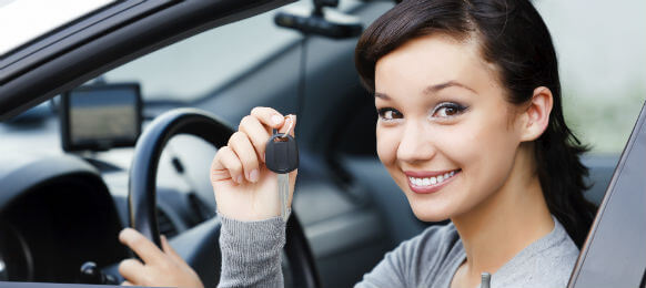 young female traveler holding the key to her car hire
