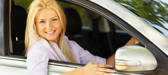 gorgeous woman smiling while riding her own car