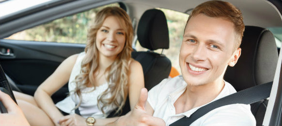 good looking couple posing inside their car
