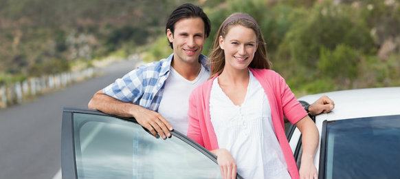 happy couple standing beside a car hire