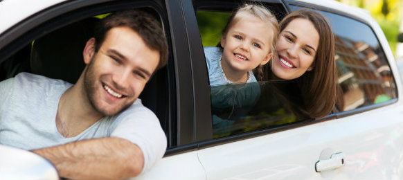 happy family posing inside their car