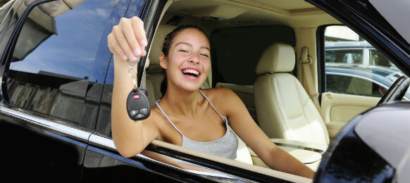 woman happily showing the key of her hire car
