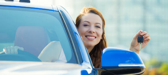 attractive lady showing the key of her rental car