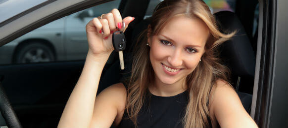 smiling young female driver showing the key to her car hire