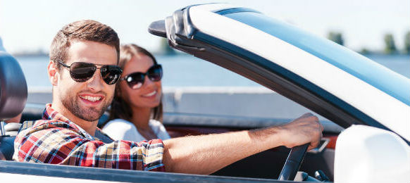 happy young couple enjoying road trip in their car hire