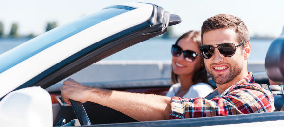 smiling traveling couple inside a rental car