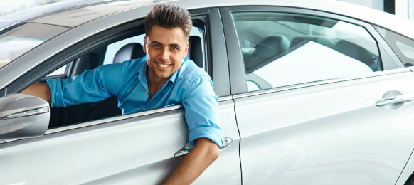 man smiling while inside his brand new car