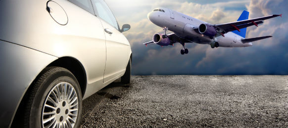 side view of a rental car and an airplane in the backgound