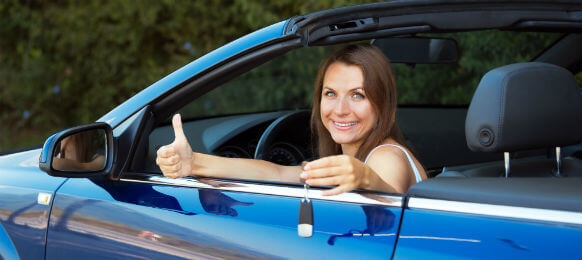smiling female traveler in a car hire