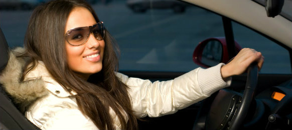 stylish woman posing inside her new car