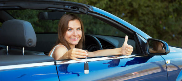 smiling woman giving thumbs up in a car hire