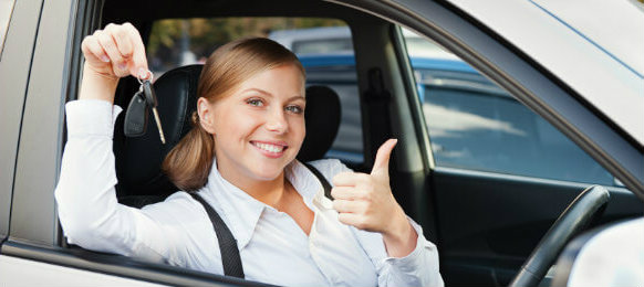 a happy woman holding a key and showing thumbs up while riding a hire car in bury