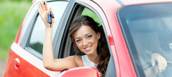 woman holding a car key in a red car