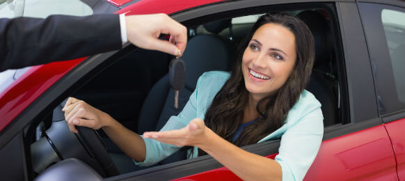 female tourist accepting the key to her car hire