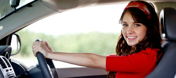 young lady in red driving a hire car
