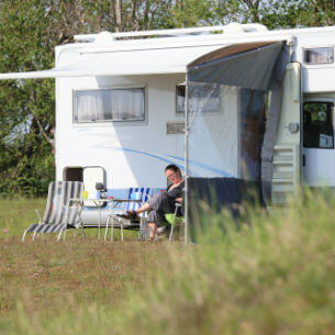 woman sitting outside a campervan reading