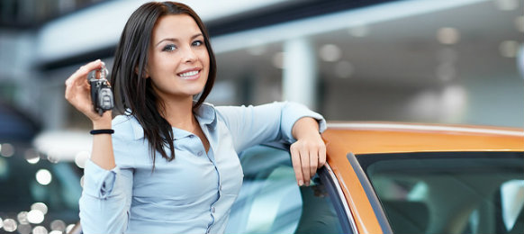 woman holding car key beside the car