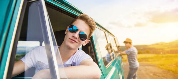 young man wearing shades looking out a hire car window