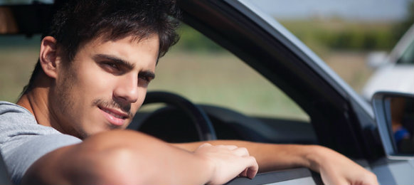 young man waiting in a car hire