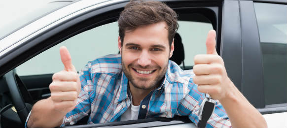 young man smiling and showing thumbs up while riding his rental car in neustadt an der weinstrasse