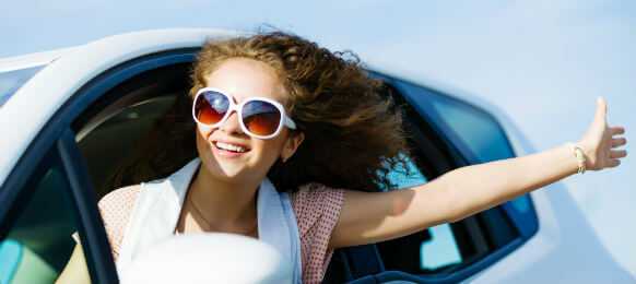 young female traveler wearing sunglasses riding a hire car