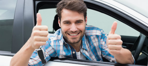 young professional giving a thumbs up sign inside his car