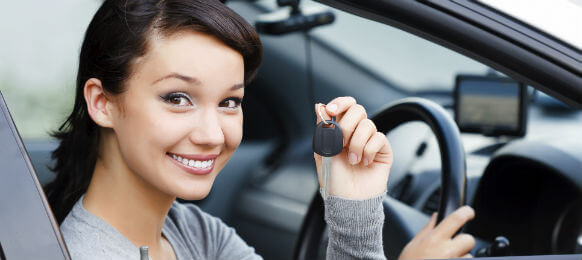 young female traveler showing the key to her hire car